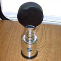 A black hockey puck proudly displayed atop a miniature Stanley Cup trophy.
