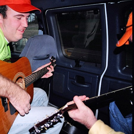 Mike and Jim playing guitars in the van.