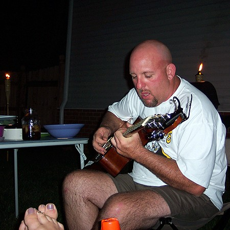 Jim strumming on his guitar.