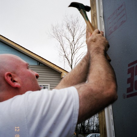 Jim nailing up siding strips on a Habitat For Humanity house.