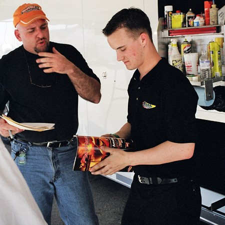 Jim showing PitPass magazine to Josh Starcher before the races in San Antonio, 2003.