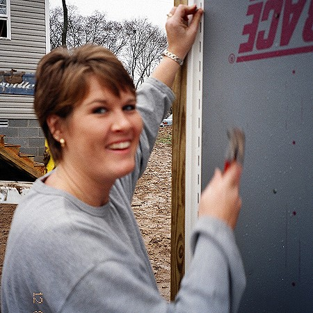 Lynnette helping to hang siding on a Habitat For Humanity house.