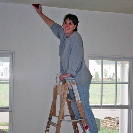 Lynnette painting the living room walls in the new house.