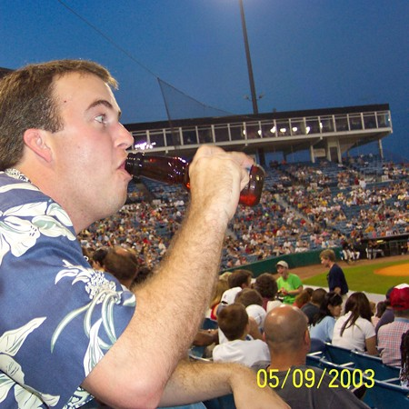 Mike drinking a beer at the baseball game.