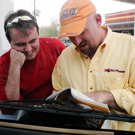 Mike and Jim looking at the map at a gas station.