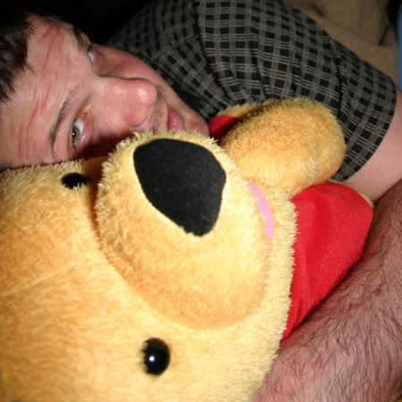Mike using Winnie the Pooh as a pillow.