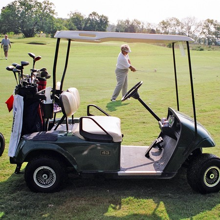 A picture of Kay framed by the golf cart as she's golfing.