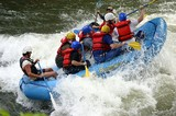 Here's a boatload of whitewater rafters plowing toward a freestyle kayaker who has scooted out of the way at the last minute.