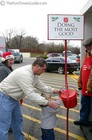 Karly stuffing a dollar in the Salvation Army bell ringer's bucket.