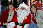 Suzie and Lynnette sitting with Santa in the mall.